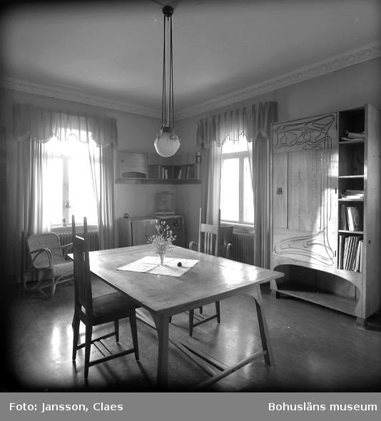 """Enligt uppgift: """"Biblioteket i 2:a plan med ursprunglig inredning. (4 karmstolar till bibliotekets bord var vid dokumentationen på reparation). Korgstol och gardiner av senare datum""""."""