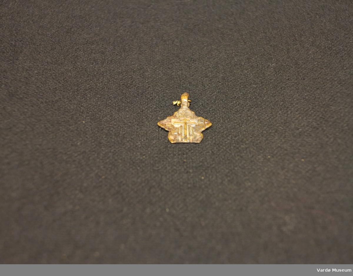 Smykke støpt av bronse. Gjenstand er støpt med Russisk ortodox kryss pa den ene siden.