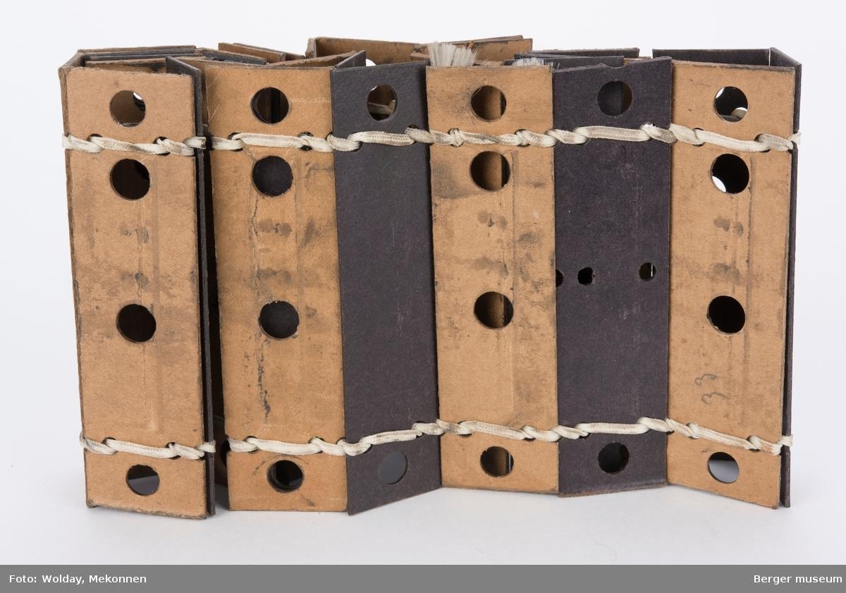 Remse av hullkort til skaftestol, 34 sammensydde kort, hvet kort er kronolgisk nummeret fra 1 til 34. Kortene er sydd sammen av en vevd tråd av synt.materiale,  og festet sammen slik at den danner en sammenhengende ring