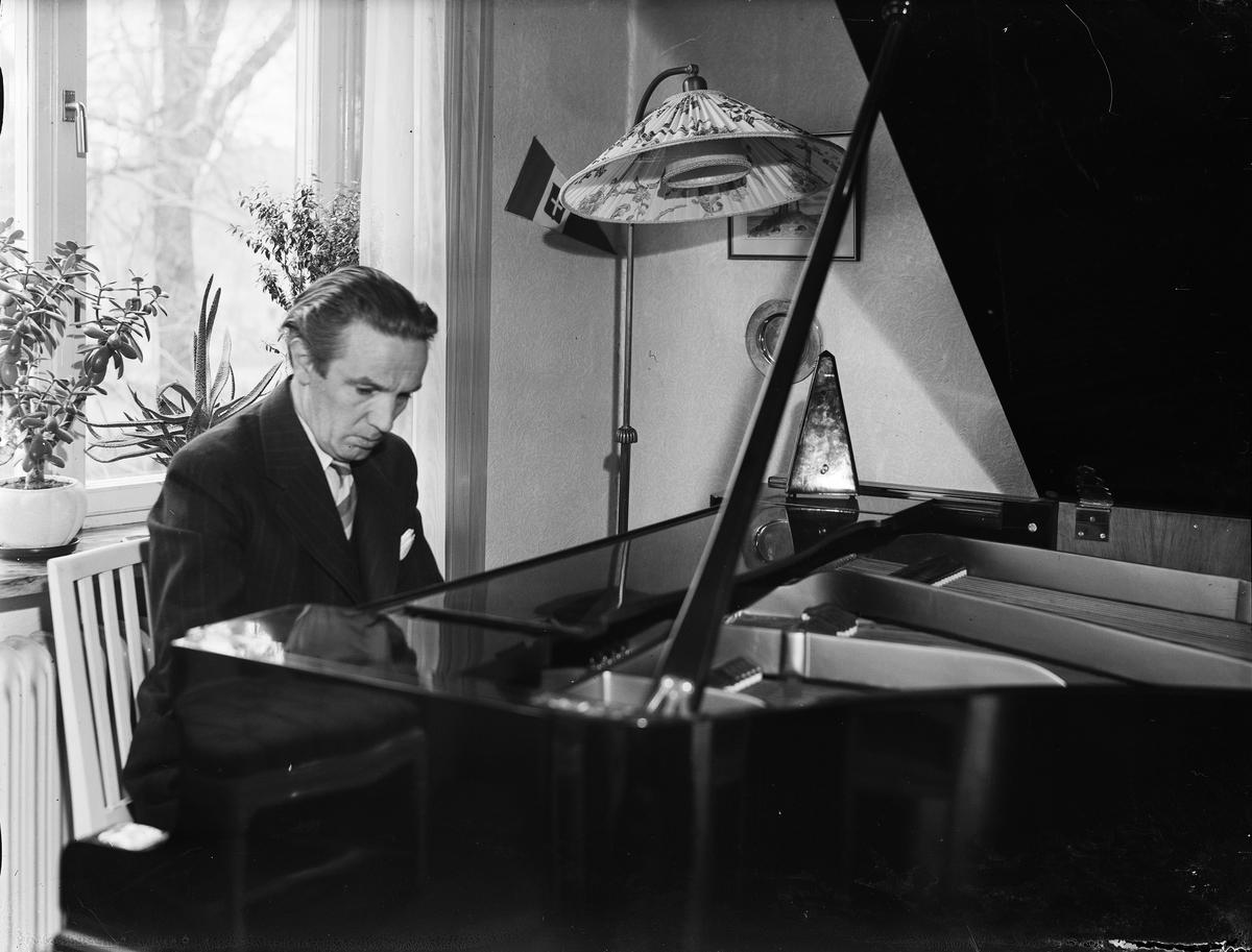 Konstnären Ågren vid flygeln i hemmet, Uppsala 1946