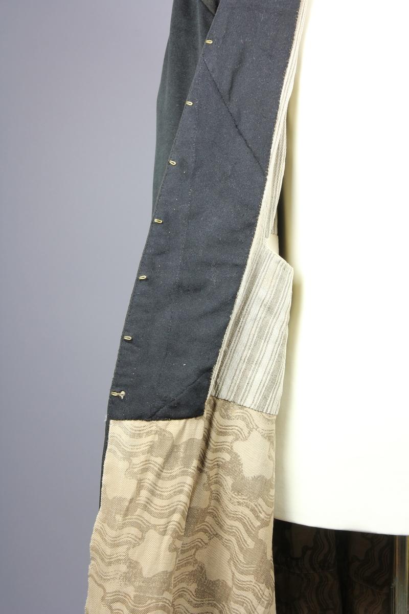 Rock av svart tuskaftsvävt yllekläde. Rocken har en 3,5 cm hög ståkrage. Ärmarna har två längsgående sömmar och 11 cm breda uppslag. Ryggstycket är sammanfogat av fyra våder. Vid axlarna är en trekantig kil infälld på var sida. Troligen en besparing. I höfthöjd har rocken en mittsöm som löper hela vägen runt. Skörten är skurna med stort omfång och rundade. I mitten bak är båda skörten förlängda med en remsa som överlappar på höger sida i ett sprund. Nederkanten har på flera ställen infälda stycken, troligen för att utnyttja tyget maximalt eller som lagningar. Rocken stängs fram med 9 par hyskor och hakar av grov mässingstråd.  Fodret är sytt av minst tre olika tyger. Överst ett grövre grårandigt linnetyg med två infällda innerfickor. Ärmarna är fodrade med oblekt linne och har vaddering av bomullsvadd. Nederst i båda ärmsluten finns rester av blåfärgade linneremsor. Kanske ett tidigare fodertyg eller ett mellanlägg. Rockens nedre foderdel är av ett tunt linne eller bomullstyg med tryckt mönster i brunt på ljusbrun botten. Möjligen är den övre delen av fodret yngre än den nedre. Slitaget på den övre är mindre än på de nedre. Hela rocken är handsydd, men det förekommer lagningar och bättringar med raksöm från symaskin. Det finns flera mindre och några större hål samt sömmar som släppt.