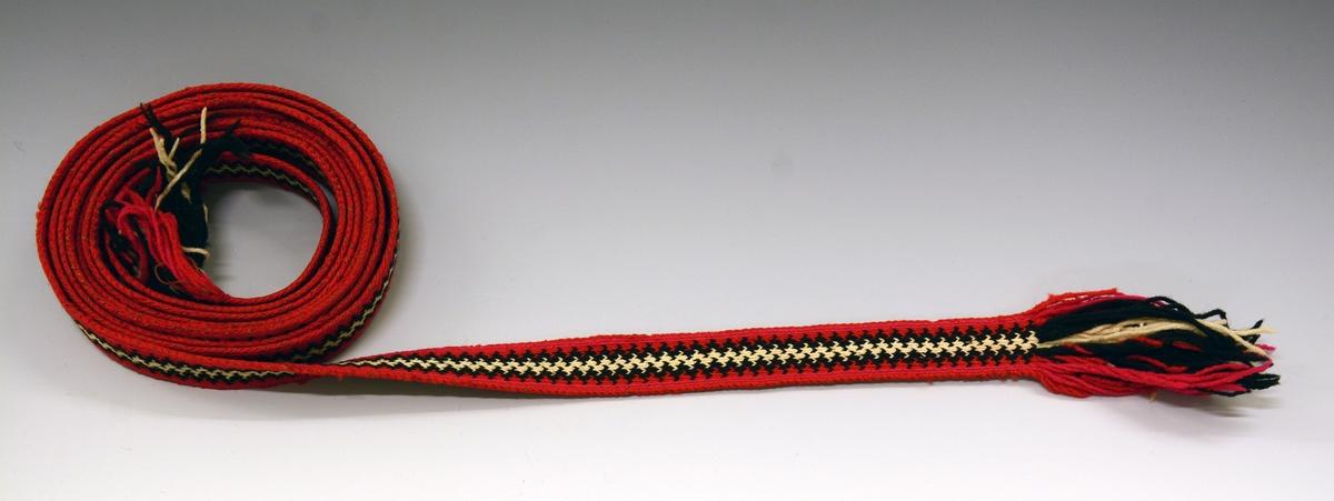 Fra protokollen: Hårband i brikkevev. Siksakbord i hvitt og svart i midten, deretter rødt, violett og ytterst rødt igjen. Frynser på 9 cm. i begge ender.