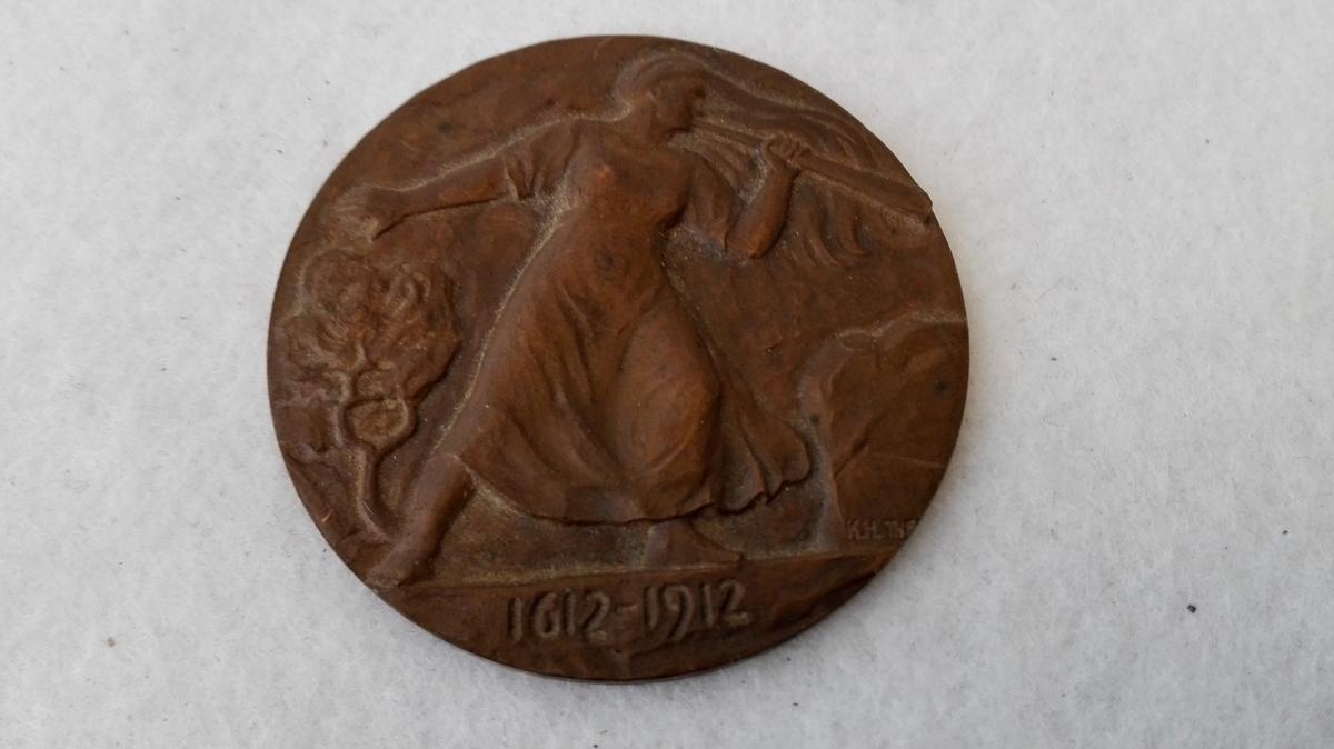 """2 erindringsmedaljer (12077 - 78).  12077 - Erindringsmedalje """"Minne um Slage i Kringom 26 august 1612"""". Paa reversen Prillar-Guri og 1612 - 1912.  Gave fra Guldsmed Karl Fridenberg, Lillehammer."""