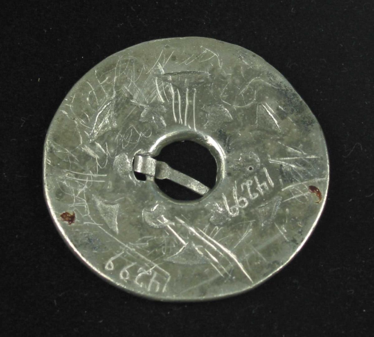 Støpt slangesølje i sølv. Bunnplata er massiv og fargen nærmest gråsvart. Tornring og gjord har rørtrådsmønster, mellom demer det et segmentfelt innerst og en krusering ytterst. Kruseringen har vekslende diamant- og knoppmønster. Et sted er to knopper stilt sammen. Et enkelt tvinnetrådsbånd skiller kruseringen fra segmentfeltet, og samme slags bånd skiller segmentene innbyrdes. Tornringen er av jern. Ingen synlige stempel.