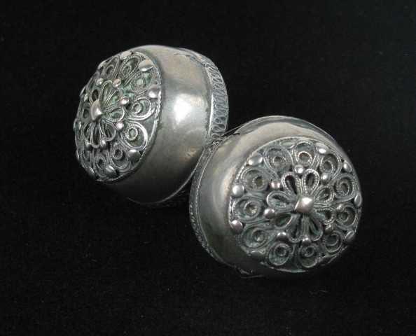 To stor sølvknapper forbundet med en ringløkke. Det brede rynkebåndet nederst er begrenset av en fin skruetråd. Knapprosetten er dobbel. Nederst er det en stor 11- løkket rosett kantet med skruetråd. Inni løkkene er det opprullet filigranstråd og i hjørnene utad flate perler. Over denne rosetten er det lagt en mindre 8-tunget rosett med knupper i hjørnene og en diamant i midten. Knappen er hul og bunnen lett buet. Påloddet løkke som er tynnslitt ytterst.