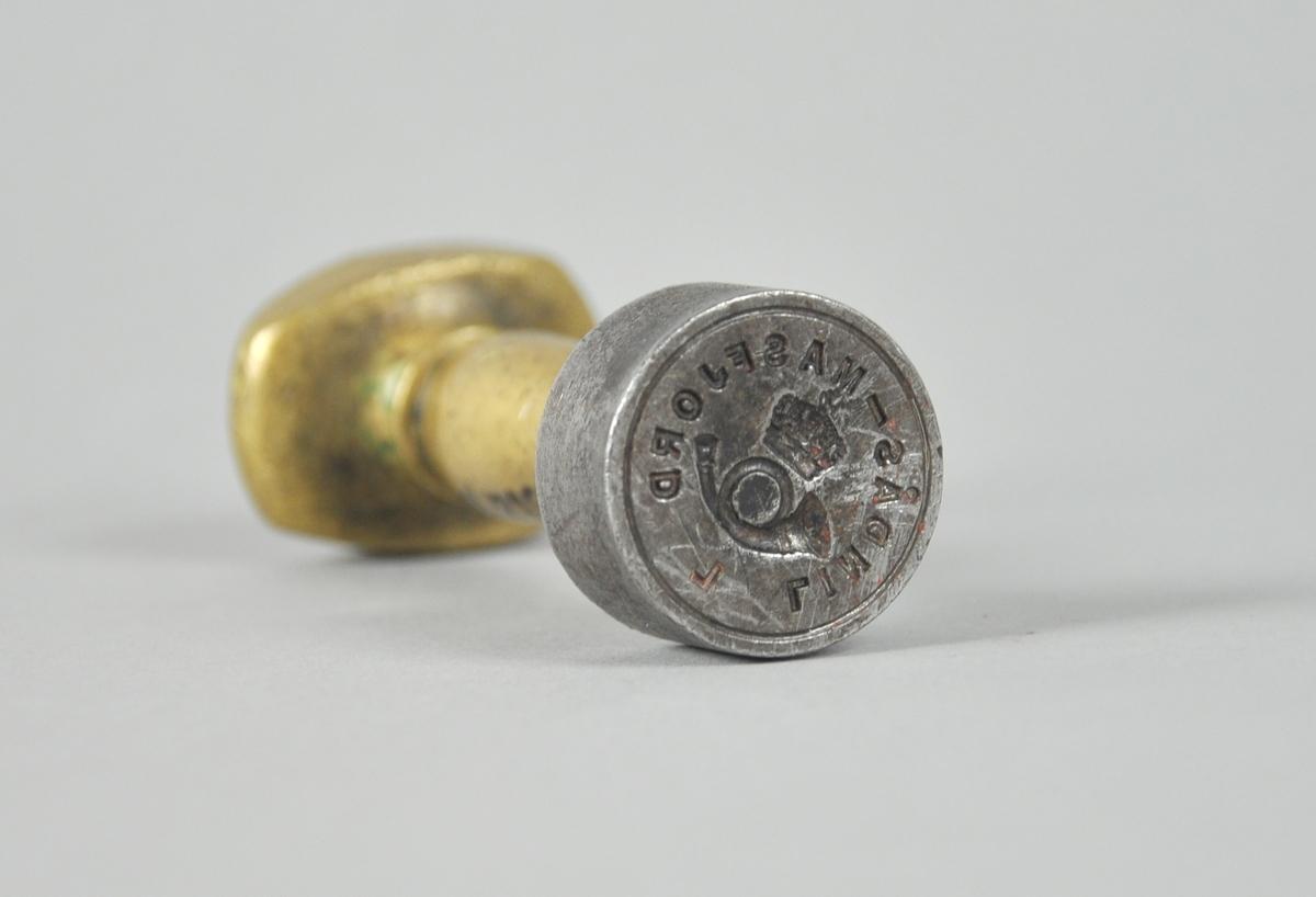 Rundt stempel av stål med posthorn og krone i sentrum og innskrift rundt kanten. Håndtak av messing.