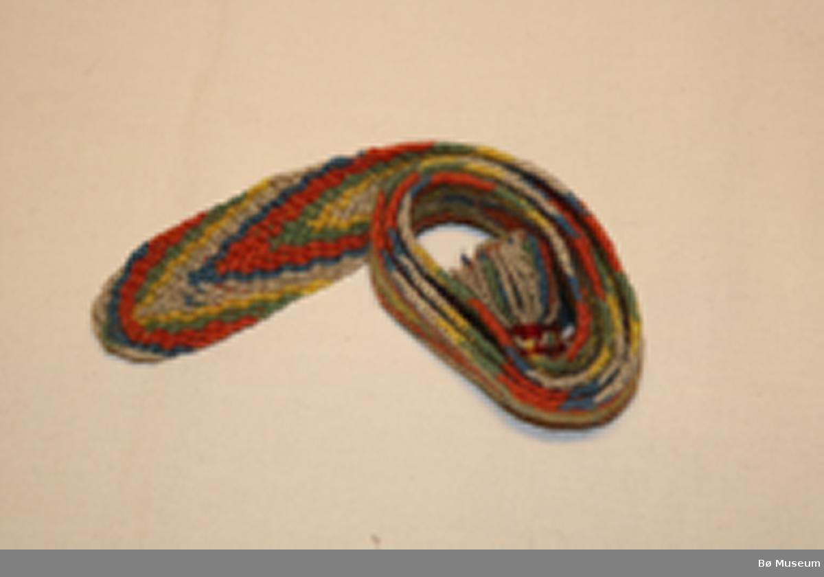 Slengt sokkeband med fleirfarga fiskebeinsmønster, søm og frynse i den eine enden. Kan vere i prøve (?) da sokkeband frå Telemark normalt sett er dobbelt så lange og har frynse i begge endar.