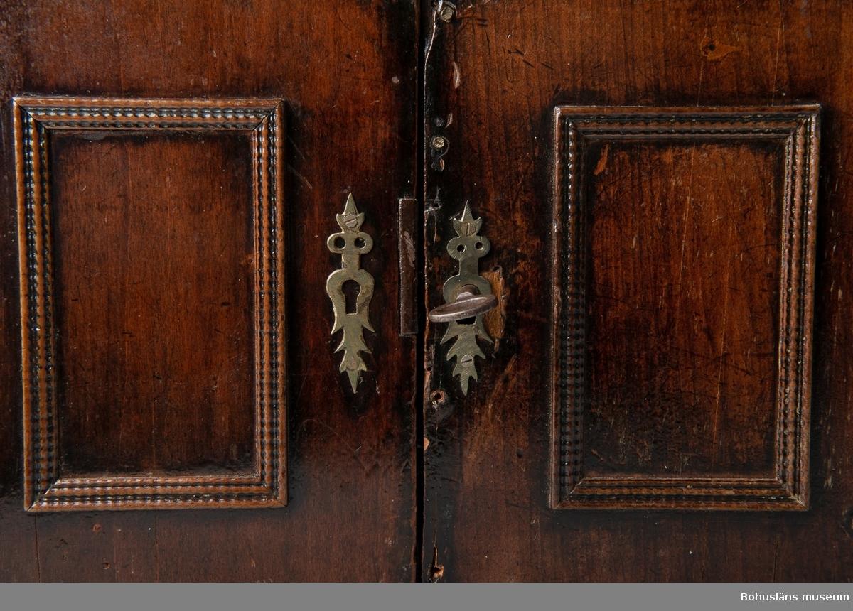 """Skåp av kabinettsskåptyp, eventuellt använt som apoteksvaror eller kryddor. Försett med dörrar med originallås och nyckel samt där innanför sex symmetriskt placerade lådor. Nedersta lådans front är uppdelad i tre liknande avsnitt så att det ser ut att vara tre lådor men det är endast en. Lådornas framsida försedda med ovala fördjupningar, där möjligen plattor eller bilder suttit. Lådorna omges av hopplist. Mindre mässingsstift med rundad huvud i lådornas nedre del fungerar som draghjälp när man ska """"öppna"""" lådan. I mittlådan som har en hög rektangulär form saknas draganordningen. Inuti är lådorna klädda med ett rödstänkt papper som i flertalet lådor är skadat eller missfärgat. Lådan i övre höger hörn är nygjord med sidor av plywood och botten av cederträ. Övriga lådor är tillverkade av furu. På dörrarnas ut- och insidor finns speglar omgivna av hopplister. På ena dörrens insida rester av målning av kinesiserande art. Nyckelskyltar av mässing av senbarockkaraktär. På kortsidorna har det funnits handtag. Endast kvar på högersidan. Skåpet utvändigt fanerat. Vattenskada på ovansidan."""