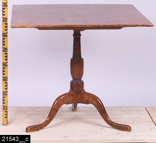 """Anmärkningar: Fällbord, Lorentz Lundelius, 1788-1805.  Nästan kvadratisk bordsskiva. Profilsvarvat ben. Tre S-formade fötter. Baktill finns en etikettsignering som lyder """"LORENTZ LUNDELIUS / Köping & Kongsöhr"""" (bild 21543__b). H:1250 Br:890 Dj:870  Bordet går att fälla upp, höjden blir då 1250 mm. I nedfällt tillstånd är det 775 mm högt (bild 21543__c). Bordsskivan är nästan kvadratisk, den ena sidan är 870 mm och den andra är 890 mm. Bordsskivan är fanerad med alrot, blindträet är furu. Alroten är fernissad. Benet och fötterna är av ljust lövträ och är också svärtade.  Mälardalen och framför allt städerna Arboga, Köping, Kungsör och Eskilstuna var under 1700-talets senare hälft och början av 1800-talet centrum för tillverkning av alrotsfanerade möbler och föremål. Här tillverkades bl.a. fällbord, byråar och olika sorters askar. Föremålen såldes inte bara inom mälardalen utan även till Stockholm och till andra länder. Det främsta namnet inom alrotsföremålsproduktionen är Jacob Sjölin (1737-1785). Alroten togs inte från alens rötter utan från stamansvällningar vid rötterna. I synnerhet vid Mälarens stränder har tillgången på detta sorts virke varit god. På slottet förvaras en kortkatalog, upprättad av f.d. antikvarie Carin Thorsén. Den upptar över 300 alrotsföremål tillhörande museer, privatpersoner etc.  Lorentz Lundelius (född?-död 1807ca), gick i lära, liksom sin broder Anders Lundelius, hos Jacob Sjölin (Brodern Anders L. flyttade till Stockholm och etablerade sig som en av den gustavianska/sengustavianska tidens största snickare). Lorentz L. gifte sig med Sjölins änka Maria Forsman 1788 och övertog därmed verkstaden. Senare tycks Lorentz ha övergivit hustrun och flyttade 1805 till Mariefred och 1807 till Södertälje. Åke Nisbeth återger i sin artikel en notis från Kung Karls dödsbok 1815 där det står att """"Escatullmakaren Lundelii av honom övergivna hustru, fattighjonet Maria Forsman, dränkt sig i sjön nedanför Kungsör."""" Mellan 1793 och 1805 var Lundelius mästare """