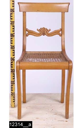 Anmärkningar: Stol, sen Karl Johan, omkring 1830  Svagt konvext överstycke. S-svängda bakstolpar. Genombruten rygg med dekorerad ryggslå. Sits av rotting. Samtliga ben är utsvängda från stolen (bild 12314__b). Undertill är stolen märkt V.R.OFF.K. (bild 12314__c), d.v.s. Västmanlands Regementes Officers Kår. H:865 Br:435 Dj:495  Enligt liggaren bestod invnr. 12314 ursprungligen av två 2 soffor och 3 stolar. Endast stolarna har registrerats av projektet Access. Inventarienumret är dock splittrat, se även invnr. 25691 och 28527 samt 28541 och 28542.  Tillstånd: Rottingsitsen är något skadad.  Negativnummer X-1948