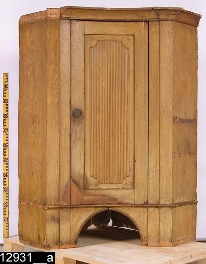 Anmärkningar: Hörnskänkskåp med öppen mellandel (överdel), almimitation, 1800-talets första hälft.  Framskjutande krön som följer skåpets form, är konkavt i mitten och avfasat på sidorna. Spegelförsedd dörr med något upphöjd räfflad dekor. Beslag i mässing och järn med kungakrona och siffrorna XIV (bild 12931__c). Profilerad list under dörren. Färgen på vänster nederdel av dörren samt området kring nyckelskylt bär spår av naturligt slitage. H:1470 Br:1160 Dj:820  Tillstånd: Skåpet saknar underdel. Delar av krönet och listen nedanför dörren är lösa (bild 12931__e). Nuvarande färg är sannolikt tillkommen under Karl Johan tid. Den imiterar alm (bild 12931__b). Ursprunglig färg är något mörkare (bild 12931__d).  Negativnummer X-1666