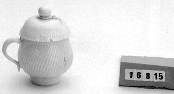 """Anmärkningar: Krämkopp med lock av porslin, Gjuten. Svängda, något bredare räfflor än föregående. Lockets fruktknopp skadad. Saknar förgyllning. Marieberg MB + blå punkt utan glasyr Steens period. H med lock 8 cm. """"Märta och Karl Adolphsons samling."""" Donation 1971 av advokat och fru Karl Adolphson Randersg. 1. Helsingborg. Negativnummer B- 6014.  Krämkoppar av porslin kom bland nyheterna vid Marieberg under Berthevins tid. De blev mycket populära under 1770-80-talen. Kallades i samband med tillverkningen geléburk och gelékopp. Liksom de flesta porsliner från Marieberg är krämkopparna gjutna. Formen är alltid densamma och oftast är mönstret med tätt ställda och svängda räfflor. Lockknoppen vanligen en frukt, någon gång en blomma. Finns helt odekorerade med en förgylld rand eller målade med blommor i flera färger.  Tidigare sakord: cremekopp"""