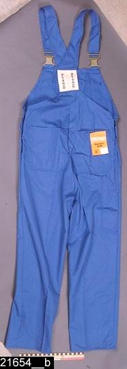 """Anmärkningar: Byxa, 1983.  Hängselbyxa av blått tyg 65% polyester 35% bomull. Byxorna har långa ben, knäpps i sidorna med två par knappar av plast, har hög skärning bak. Baktill är två långa hängselband fästa vid en bred resår. Namnet Slitman är ivävt i resåren. Framtil finns en bröstlapp med tredelad ficka, en av fickorna har lock. Upptill på bröstlappen finns två spännen av plast """"fixlock"""", motsvarande spännen är fästa på hängselbanden. Byxorna har två påsydda fickor fram och två, förstärkta, bak samt vid höger sida en smal och lång ficka. Gylf med tryckknappar av metal. Byxan har storlek 48, art 4528. Tryck i vitt på bröstlappens mittficka i form av en krona samt texten Skultuna. Invändigt finns en lapp med texten Enköpings kemtvätt.  Bild 21654__a visar framsidan av byxan. Bild 21654__b visar baksidan av byxan.  Tillstånd: Nyskick.  Historik: Inköpt från Gränges aluminium i samband med samtidsdokumentationen där 1983. Byxmodellen har använts av valsare, spolare, avsynare, skrotpressare, rörkapare, verkstadspersonal på Skultuna messingsbruk. Byxan är tillverkad av Slitmanfabriken AB, Sala."""