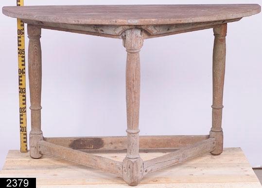 Anmärkningar: Väggbord, 1700-talets senare hälft.  Halvmåneformad bordsskiva. Fyra profilsvarvade ben. Tre fotslåar som är profilerade i över- och underkanterna. Fotslåarna bildar tillsammans formen av en triangel. H:765 Br:1240 Dj:655  Hela bordet är gråmålat och bär spår av naturligt slitage. Nästan ingen färg finns kvar på bordsskivan.  Tillstånd: Bordet är i mycket dåligt skick och är framför allt mycket rangligt. Låspinnar för bordsskivan saknas.  Historik: Från Halvarstorp, Tärna sn. Inköpt genom intendent Sven T. Kjellberg.