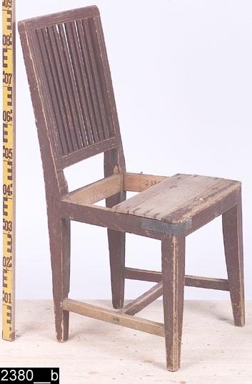 Anmärkningar: Stol, gustaviansk modell, omkring 1800.  Överstycke, bakstolpar och ryggslå är kälade. Kälningarna går in i varandra (bild 2380__c). Genombruten rygg med tio räfflade ryggspjälor. Kannelyrliknande dekor på bakstolparna precis intill sitsen (bild 2380__c). Sits av trä. Samtliga sargar är avfasade i nederkanterna. Fyra nedåt avsmalnande ben (bild 2380__b). Ett H-kryss förbinder benen. H:885 Br:480 Dj:480  Invnr. 2380 bestod ursprungligen av tre poster. Enligt en äldre registrering saknas en post. En av posterna har, av projektet Sesam, fått invnr. 25684.  Hela stolen är av ljust lövträ utom ryggspjälorna, delar av sitsen, sidosargarna och två slåar i H-krysset vilka är av furu. Stolen är mörkröd och bär spår av naturligt slitage.  Tillstånd: Sitsen är trasig. Förstärkning i järn mellan framsargen och vänster framben.  Historik: Inköpt av Intendent Kjellberg på platsen 1921.