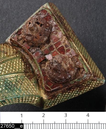 Anmärkningar: Badelunda sn, Tuna undersökt 1952-1953 Spänne från båtgrav daterad till yngre järnålder, ca 800 e.Kr. (Vendeltid/Vikingatid)  Ryggknappsspänne av förgylld brons med granater från grav 35. Alla  kanter på spännet är ornerade med rutmönster liksom bågens översida, som dessutom är fältindelad genom två pärlande band (bild 27650__d). Plattorna har granatinläggningar och knoppar av organiskt material (bild 27650__e). Kronan är halvsfärisk, genombruten och bildad av en kvadrat med utdragna hörn. Kronan är ornerad med bandflätning och i kors däröver lagda band med stämpelornering (bild 27650__f).  Vid nålfästet och på nålen finns textilrester (bild 27650__c). L 170 mm Br 45 mm Nålens L 91 mm Utställd Forntid 2014.   Litteratur Nylén, E. & Schönbäck, B. 1994. Tuna i Badelunda. Guld kvinnor båtar I. Västerås kulturnämnds skriftserie 27. Västerås. s 36 ff  Nylén, E. & Schönbäck, B. 1994. Tuna i Badelunda. Guld kvinnor båtar II. Västerås kulturnämnds skriftserie 30. Västerås. s 94 ff, 150ff, 199.  Färgfoto: A-7424, Sv/v A-7297, A-7298 in situ, fotograferad teckning neg nr A-7405, hologram