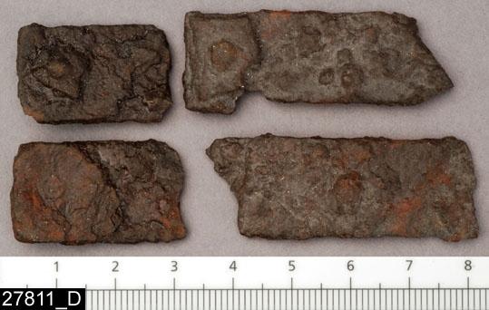 Anmärkningar: Badelunda sn, Tuna undersökt 1952-1953 Betselutrustning, från brandgrav daterad till yngre järnålder, ca 1000 e.Kr. (Vikingatid).  Beslag av järn, från grav 2. Minst 4 st rektangulära, delvis fragmentariska beslag. De har en kort nit med kvadratisk nitbricka i varje ände (Se även invnr 27811D). Beslagen har använts till att pryda ett betsel.  L ca 49 mm Br ca 31 mm  Litteratur: Nylén, E. & Schönbäck, B. 1994. Tuna i Badelunda. Guld kvinnor båtar I. Västerås kulturnämnds skriftserie 27. Västerås. s 94 ff Nylén, E. & Schönbäck, B. 1994. Tuna i Badelunda. Guld kvinnor båtar II. Västerås kulturnämnds skriftserie 30. Västerås. s 10 ff, 199  Fotograferad teckning A-7384,  A-7389