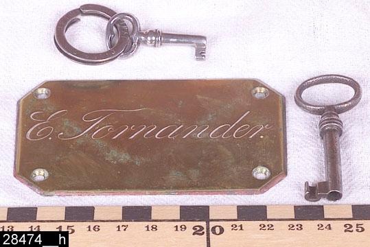 """Anmärkningar: Klaffbyrå, oscariansk/nyrokoko, 1800-tal.  Rektangulär skiva överst med rundade hörn. Framkskjutande lister på fronten och sidorna med godronnliknande dekor. Därunder finns en buktande och S-formig klaff (bild 28474__b) med en nyckelskylt i järn (bild 28474__c). Genom att trycka på två järnknappar på insidan kan man fälla ned klaffen (bild 28474__d). Invändigt finns sex lådor med svarvade knoppar av ben (bild 28474__e). I mitten en låsbar lucka med nyckelskylt av ben. På skrivdelen en påklistrad pappersbit med följande text: """"Denna byrå har tillhört Nina Maria Bergh, gift Fornander (född i västerås 20 febr. 1874 - död i Stockholm 22 juni 1944) dotter till boktryckare Adolf fredrik Bergh (född i Västerås 10 dec. 1831 - död i Västerås 13 jan 1905) och hans maka Thecla Wilhelmina Bergh, född Hedenström (född i Skultuna 15 juli 1833 - död i Västerås 10 juni 1908 / till Länsmuseet Västerås"""", (bild 28474__f). Under klaffen finns ytterligare två draglådor med nyckelskyltar av järn, den mellersta draglådan är indelad i tre fack (bild 28474__g). På flankerna om draglådorna finns profilsvarvade halvkolonner. Fyra profilsvarvade ben. H:825 Br:865 Dj:465  Större delen av möbeln är fanerad. Lådfronterna och skivan längst upp är fanerad med almrot. Sidostyckena och halvkolonnerna är av massiv alm. Ovanför halvkolonnerna finns rundade stycken som är fanerade med almrot (möjligen valnöt). Inredningen, bakom klaffen, är fanerad med alm. Blindträet i klaffbyrån är furu. I den nedersta draglådan ligger två nycklar (som passar till låsen) och en dörrskylt i mässing där det står """"E Fornander"""", bild 28474__h.  Historik: Bygger på en tidigare registrering (2005) av föremålsantikvarie Roy Cassé: Gåva från Margareta Fornander, Stockholm. I byrån låg två fotoalbum, två almanackor (1874-1875), samt två inramade fotografier invnr. 28482, 28483. Har ursprungligen stått i Nina Maria Berghs barndomshem på Stora gatan 58 i Västerås (se skiss bland bilderna till invnr 27798). Nina Mar"""