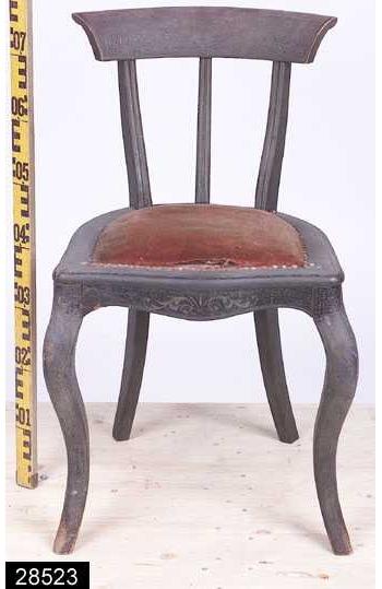Anmärkningar: Stol, svart, omkring 1900.  Konvext överstycke med snedställda kanter. Genombruten rygg med S-svängda bakstolpar och en S-svängd ryggståndare (jämför bild 2442__b). Svagt sköldformad sits med stoppning som är fäst i stolen med nitar av mässing. Kontursågad framsarg. S-svängda framben (jämför bild 2442__b). Överstycket, bakstolparna, ryggståndarna, framsargen och frambenen är försedda med en sgrafitto-liknande dekor i guldfärg (jämför bild 2442__c). H:735 Br:460 Dj:485  Invnr. 28523 ingick ursprungligen i invnr. 2442, vilket har splittrats av projektet Access vid dess genomgång av bl.a. stolar 2006. Observera att bilderna är attribuerade till den identiska stolen med invnr. 2442. Den sgrafitto-liknande dekoren har mörknat kraftigt. Den har ursprungligen sannolikt varit betydligt klarare.  Historik: Gåva av körsnär Grönberg, Västerås, 1921. Inköpta från Strömsholms slott.