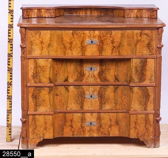 """Anmärkningar: Byrå, oscariansk, omkring 1900.  Konturerad uppsats med lådor på flankerna. Svagt konturerad skiva med profilerade kanter. Fyra draglådor med nyckelskyltar av järn. De tre nedersta draglådorna är inskjutna i mitten. De främre hörnen är försedda med skurna akantusflikar samt kannelyrer (bild 28550__b). Fyra klossformade konturerade fötter. På baksidan finns en etikett där det står """"C. Er. ERICSSON. / SNICKARMÄSTARE. / WESTERÅS."""" (bild 28550__c). H:940 L:990 Dj:550  Större delen av byrån är fanerad med valnöt, blindträet är av furu. Lådfronterna är av massiv valnöt. Ovandelen (skivan) av uppsatsen är av massiv mahogny. Tillstånd: Lådorna på uppsatsen saknar dragknoppar och går inte att öppna. Nycklar saknas till samtliga draglådor. En nyckelskylt är trasig."""