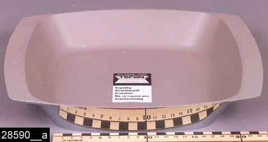 """Anmärkningar: Form, omkring 1971.  Fyrkantig form med svagt böjda kanter. Formen är av aluminium men invändigt är den försedd med teflon. I botten finns en lapp som anger att formen är försedd med teflon (bild 28590__b). Undertill finns en märkning, """"25 cm"""" (bild 28590__c). I formen ligger ett brev från Gränges, daterat 11/3-71. I brevet framgår att formen är en prototyp som aldrig kom i produktion (bild 28590__d). H:50 Br:250 L:290  Tillstånd: Nyskick.  Historik: Gåva från SAPA AB, Division Service, 2002. Föremålet stod i ett skyddsrum på bruksområdet i Skultuna."""
