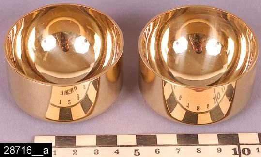 """Anmärkningar: Supkopp (2st), 1970-tal eller senare.  Runda och skålformade supkoppar av mässing med 23 karats förgyllning. Undertill är de märkta """"SKULTUNA 1607 Sweden P. Forssell"""" (bild 28716__b). Pierre Forssell var formgivare på Skultuna 1955-1986. Till supkopparna hör en originalförpackning (bild 28716__c). I förpackningen ligger en broschyr om supkopparna (bild 28716__d). Supkopparna är avbildade i kataloger från Skultuna fr.o.m. 1970-talet. År 2007 var de fortfarande i produktion. Enligt en broschyr, utgiven av museet 2007 och benämnd """"Skultunastämplar 1800-2000"""", började den typ av stämpel som finns på föremålet användas 1922. Den användes fortfarande år 2007. H:35 D:60  Tillstånd: Nyskick.  Historik: Gåva från SAPA AB, Division Service, 2002. Föremålet stod i ett skyddsrum på bruksområdet i Skultuna."""