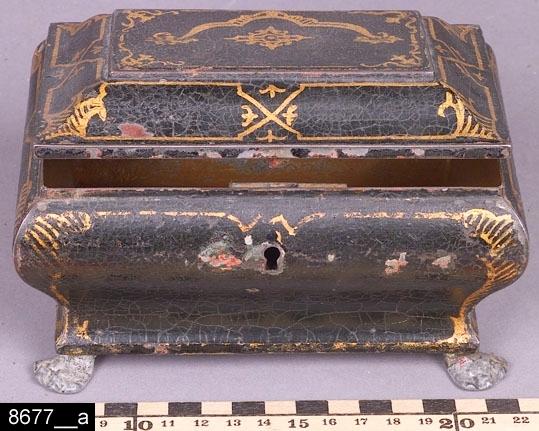 Anmärkningar: Skrin, omkring 1900.  Gångjärnsförsett avfasat lock. På framsidan finns ett nyckelhål, nyckel finns (bild 8677__b). Invändigt är skrinet brunmålat (bild 8677__c). Fyra tassformade fötter. Hela skrinet är bukigt i formen och är försett med en dekormåleri i svart och guldfärg. H:85 B:155 Dj:110  Historik: Gåva från fältläkare Gunnar Wingren, Västerås.