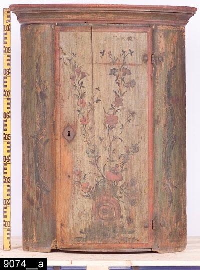 """Anmärkningar: Hörnskåp (överdel), 1700-talets andra hälft.  Framskjutande rundat krön. Enkeldörr med rokokomåleri bestående av en blombukett med en stor röd ros nederst och utskjutande röda och blåa blommor uppåt. Blommorna längst upp till vänster är klockformade. På dörren finns en nyckelskylt i järn. Färgen på vänster sida av dörren bär spår av naturligt slitage. Dörren flankeras av målade kartuscher i grön camïeu (målning i olika nyanser med samma färg) med konturstärkande inslag av svart färg (bild 9074__c). Invändigt ett lås i järn och tre hyllplan. Tillhörande nyckel i järn (bild 9074__d). Det översta hyllplanet är kraftigt indraget. Det mellersta är något indraget och konkavt (bild 9074__b). H:1130 Br:855 Dj:535  Tillstånd: Skåpet har haft en underdel (dock är det enligt kortkatalogen inköpt endast som överdel).  Historik: Köpt i auktionshandel i Arboga. Det inköptes någon gång under 1930-talet. (Tillverkningstidsangivelse infogad på grundval av att skåpet har deltagit i utställningen """" Samlat 1700-tal """" MLOO, 1986-08-25).  Negativnummer X-1692"""