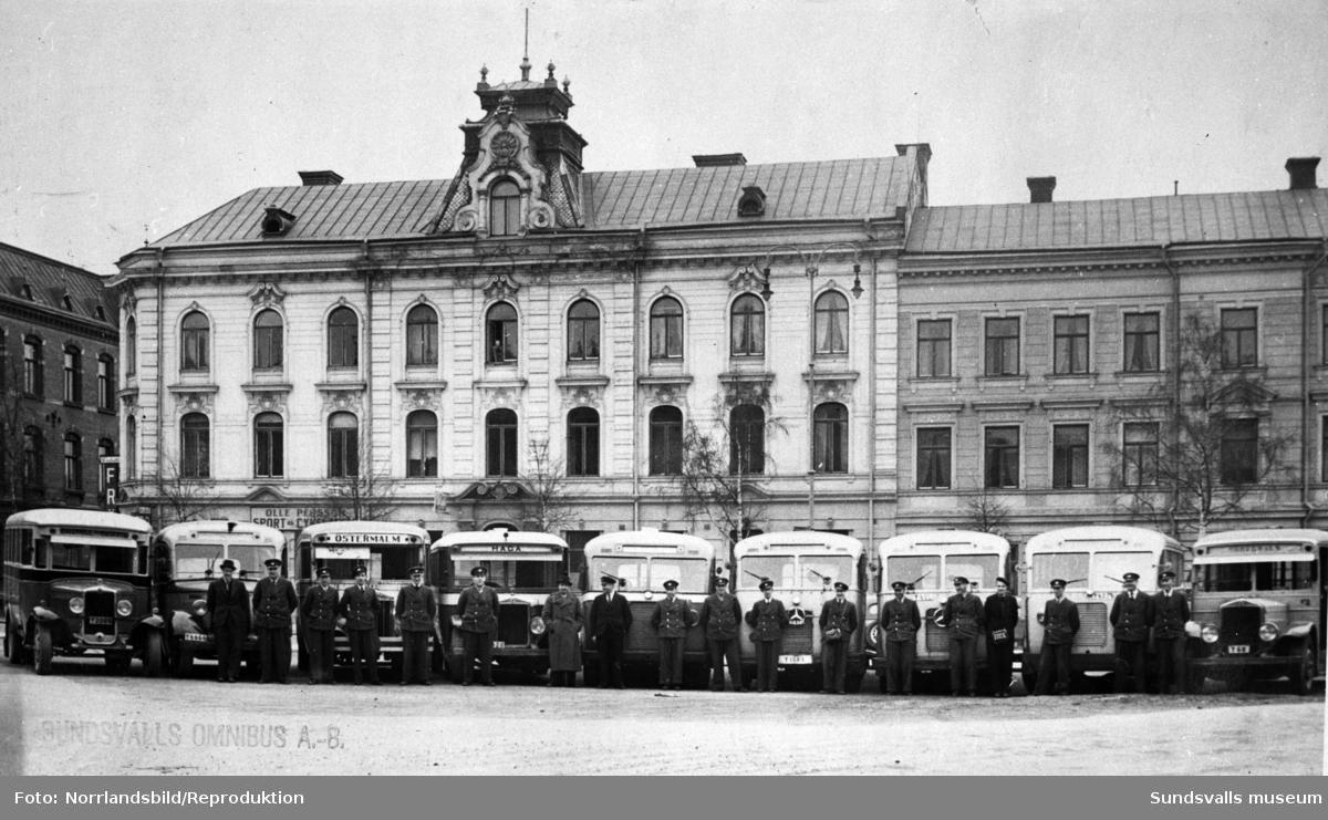 Bussar och busschaufförer uppställda på Nytorget. Köpmangatan och kvarteret Brutto bakom. Reprofotografi för AB Hagabussarna.