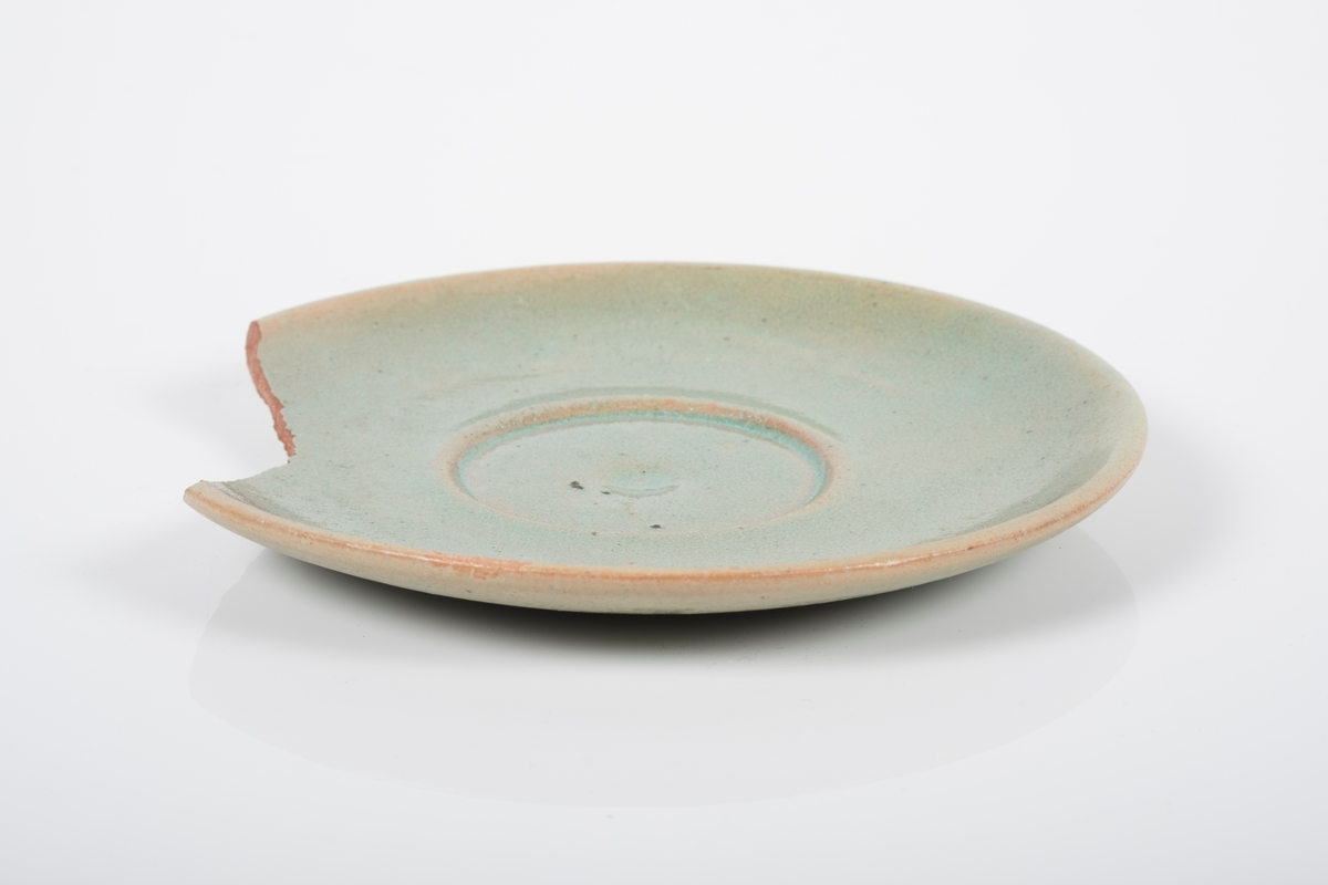 Skål i keramikk med grønn lasur. Spor etter tre knotter på bunnen, usikker funksjon. Bunnen har matt overflate. En brukket del av skålen mangler.