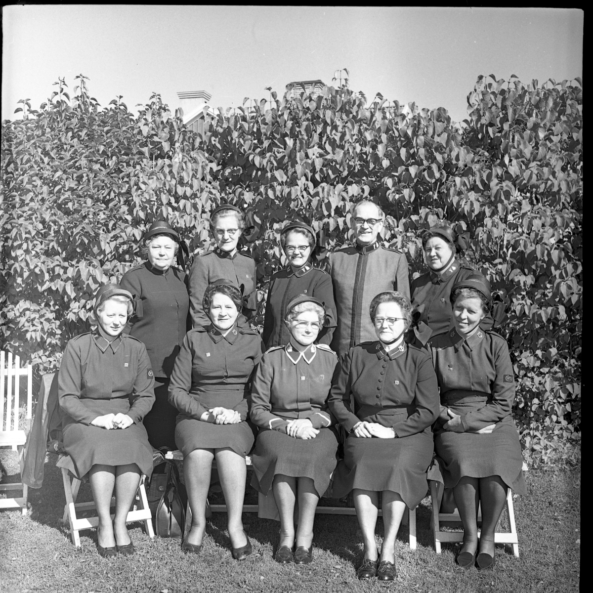 En grupp okända frälsningssoldater, varav en manlig. Sittande och stående för gruppbild.