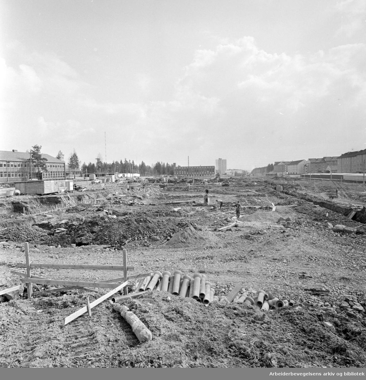Lambertseter. Småindustri mellom Cecilie Thoresens vei og trikkeskinnene. Nedenfor kjøpesenteret graves det for industribygg for OBOS. April 1965