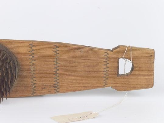 Anmärkningar: L; 630 S. br 114 Spolformad bräda av trä med prof. handtag med halvmånformiga utskärningar. Mitt på plattan en järnbeslagen rund träplatta besatt med järnpiggar. Brädan har sparsam karvsnittsdekor. Gåva av fröken Anna Thunell. Blåsbo. Västerås