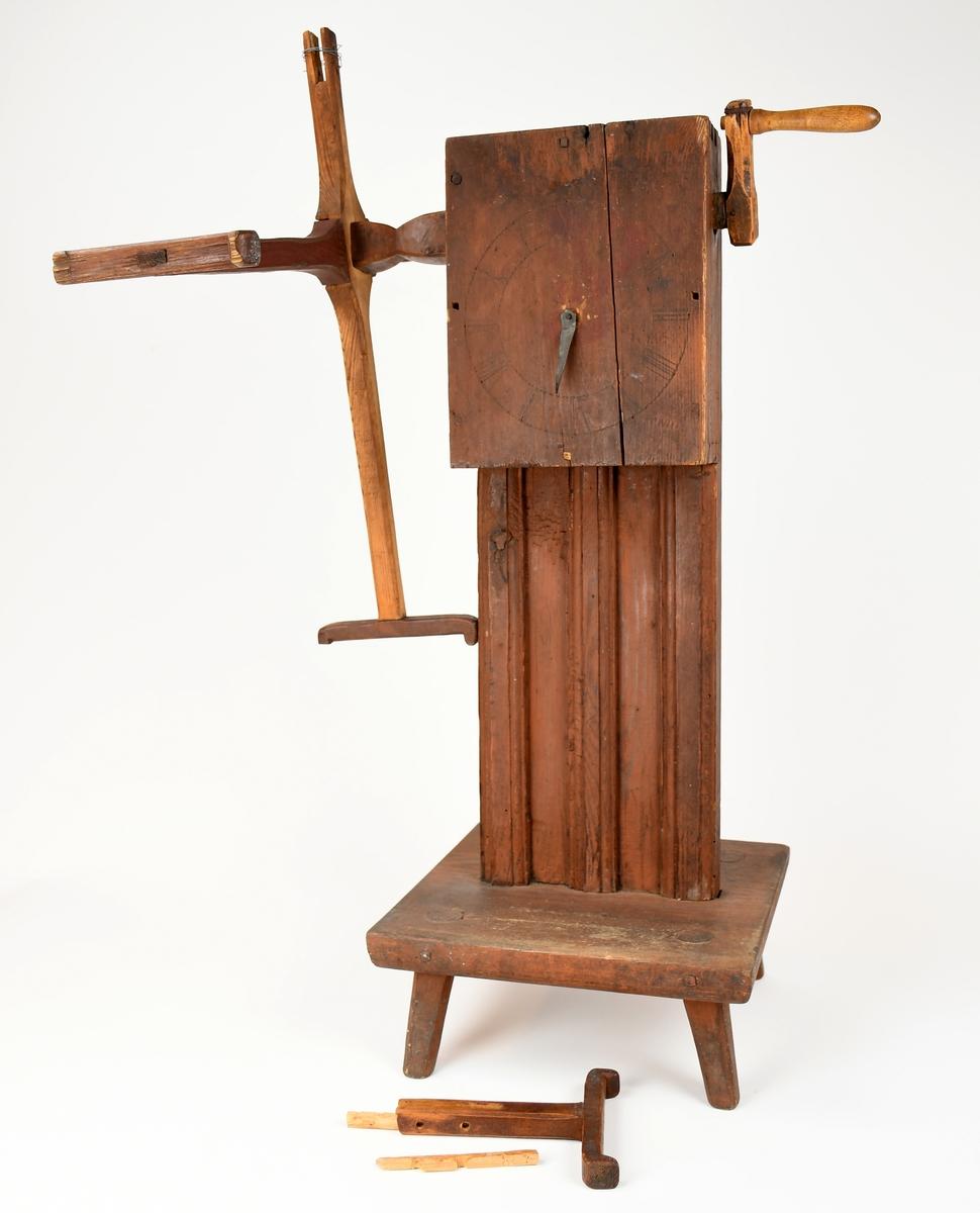 Anmärkningar: Knäpphärveln står på en 4-kantig platta med 4 st itappade fötter. Ståndaren är en platt, bred planka på vilken lådan med slagverk och vevarm är fästade. Härveln rödmålad. Urtavla framtill med visare för att räkna antalet trådvarv. Sinkade kanter och fyrkantig träplugg håller ihop stommen. H. 700 Härvelns diam. 620