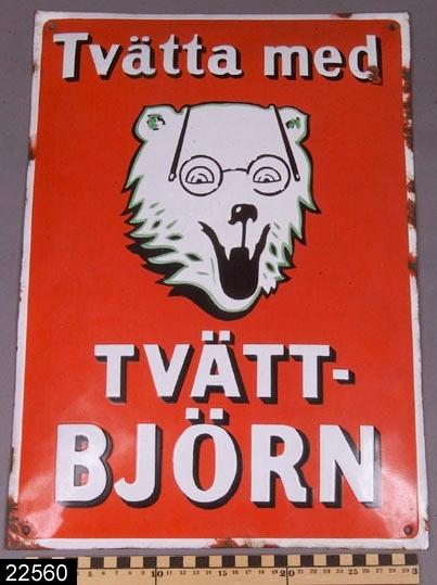 """Anmärkningar: Skylt, 1900-tal.  Bukig rektangulär skylt med björnhuvud i vitt samt text """"Tvätta med TVÄTT-BJÖRN"""" mot röd botten. H:460 Br:325  Tillstånd: Emaljskador.  Historik: Gåva från Stig Eriksson, Backa 2, Hedensberg, 1986. Skylten har suttit i handelsboden i Backa, Hedensberg, Tillberga sn."""