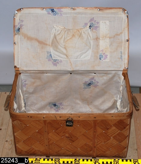 """Anmärkningar: Koffert, 1900-tal.  Gångjärnsförsett platt lock med ett handtag. På framsidan finns en järnhank och ett tillhörande lås med texten """"KAMP"""" och """" MADE IN GERMANY """". På kortsidorna finns handtag. Invändigt är kofferten klädd med blommigt tyg, där finns också en ficka på insidan av locket (bild 25243__b). På ena kortsidan fraktlappar """" Westanfors """" , """" Storvik """" , """" Gäfle central"""". H:350 L:680 Dj:355  Historik: Gåva från Britta Ringström, Hedkärra, Västanfors sn, 1992."""