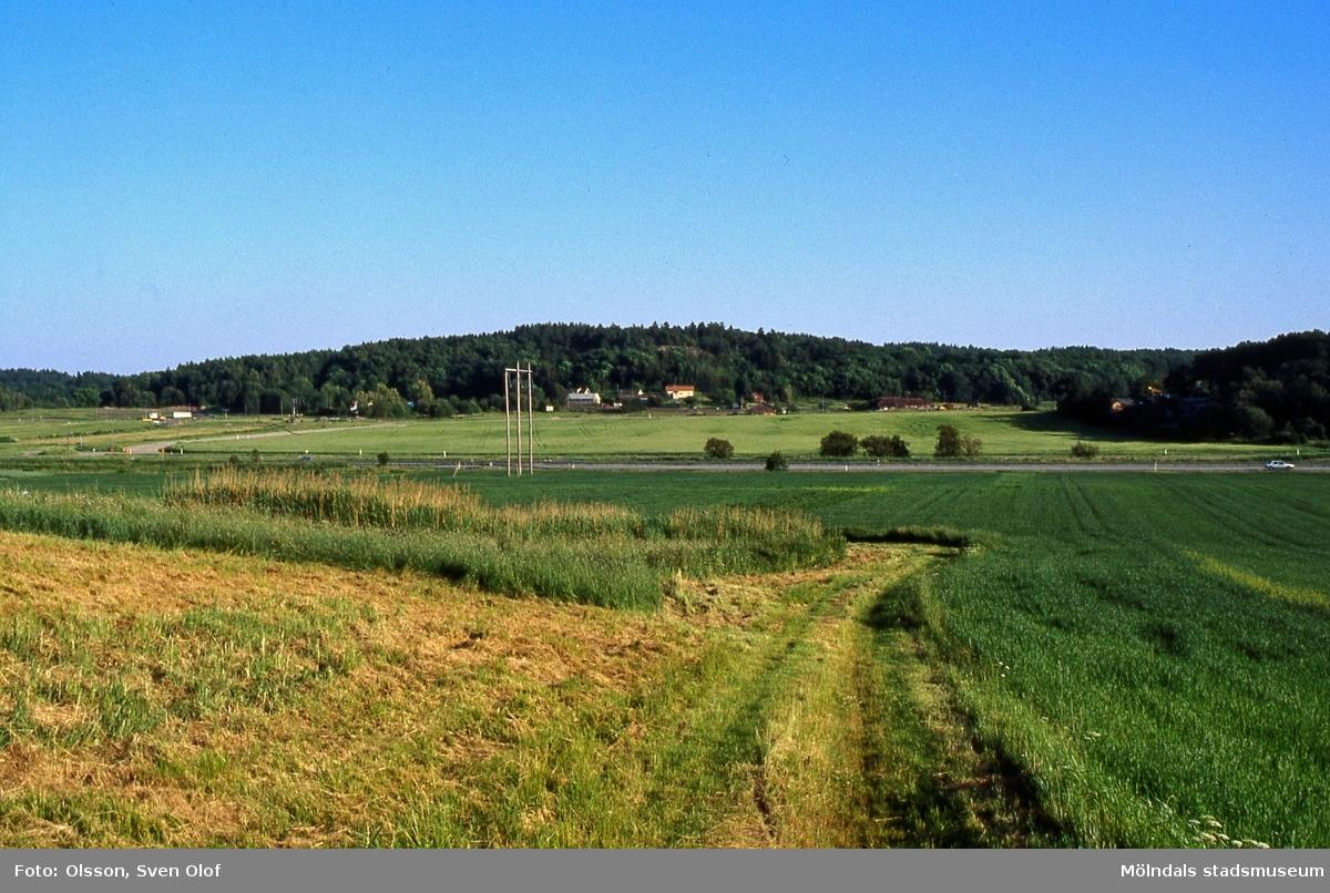 Vy från Fässberg mot Balltorp, Mölndal, i juli 1991. Söderleden går genom landskapet. FD 4:32.