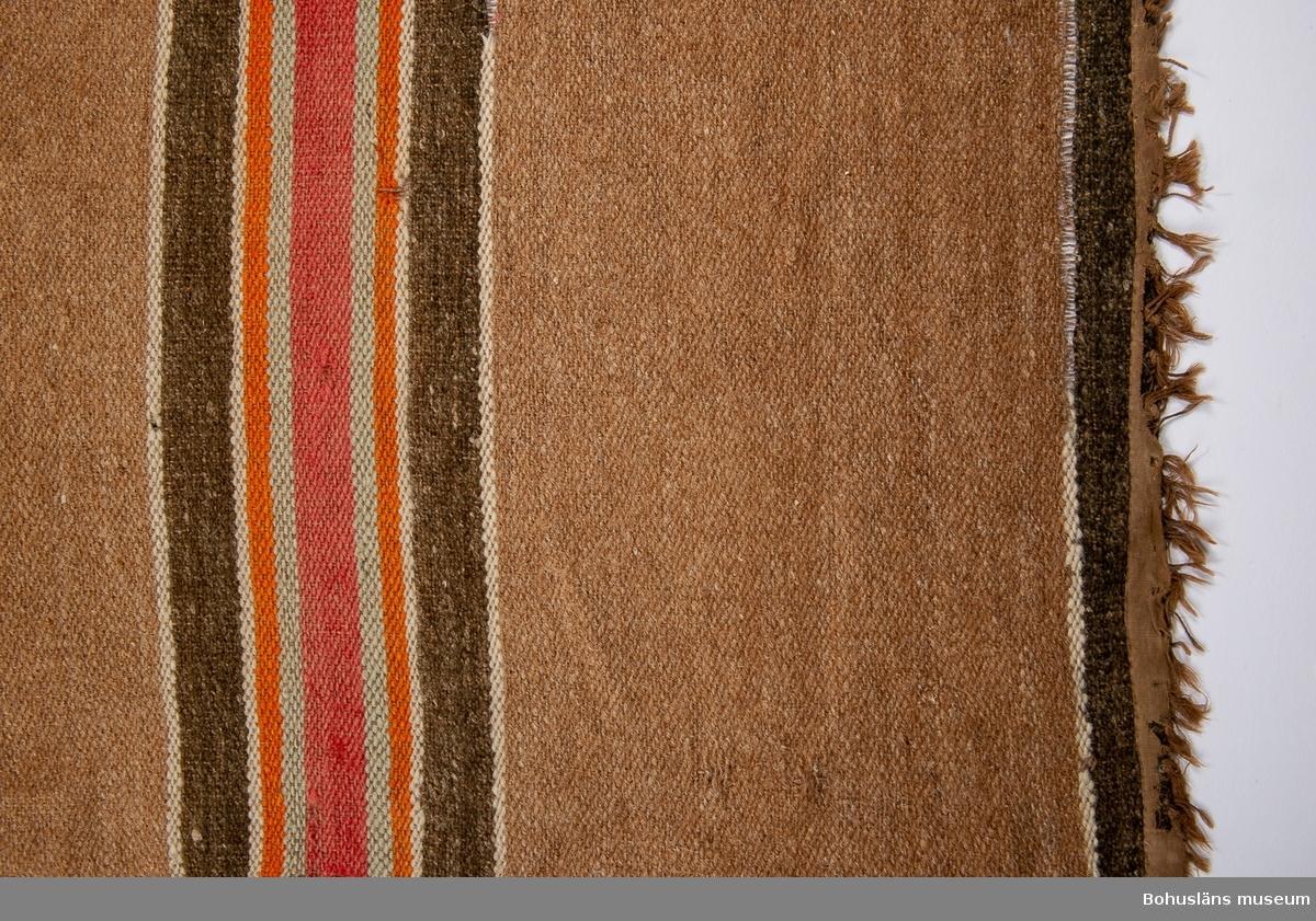 Beige-brun. Tvärrandig i rött, ljusblått, orange, vitt och grått. Denna matta är en av fyra stycken som låg i en fyrkant i salen hos givarens mormors mor på Orust från ca 1890 och framåt tiden. Se bilaga i Bilagepärmen.