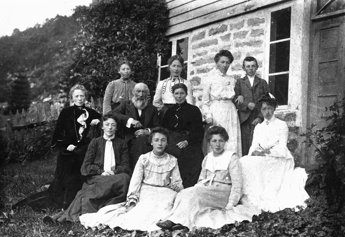 Gruppefotografi av en familie i hagen utenfor et hus. Knut D. Stafset med familie.