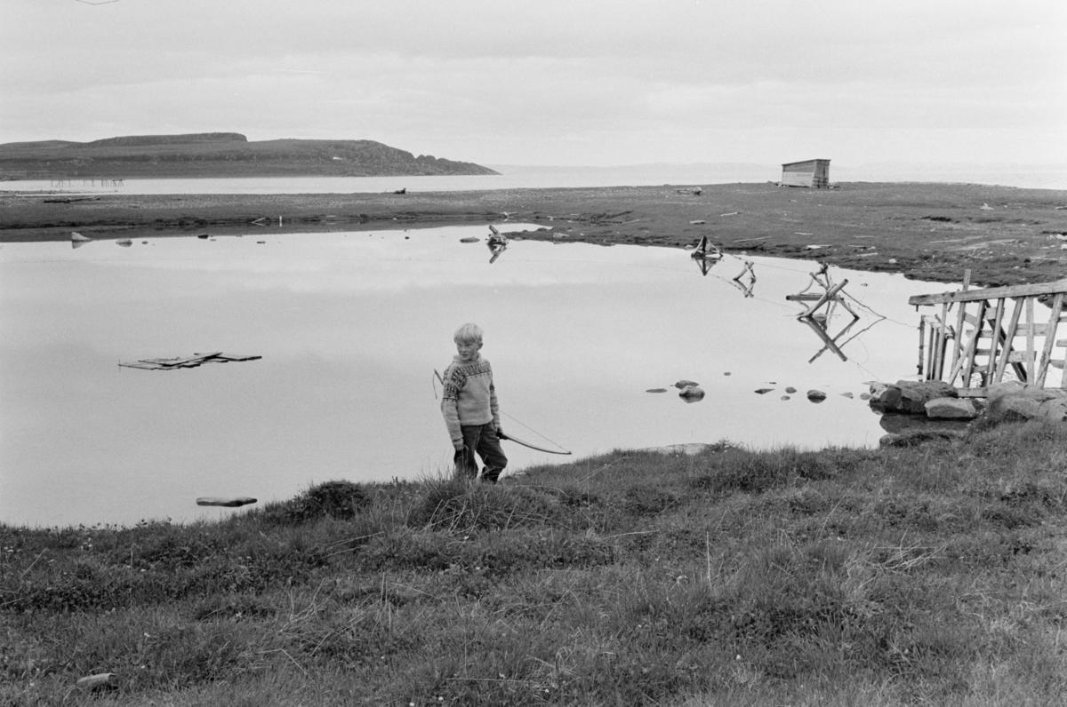 En gutt med pil og bue ved i et kystlandskap