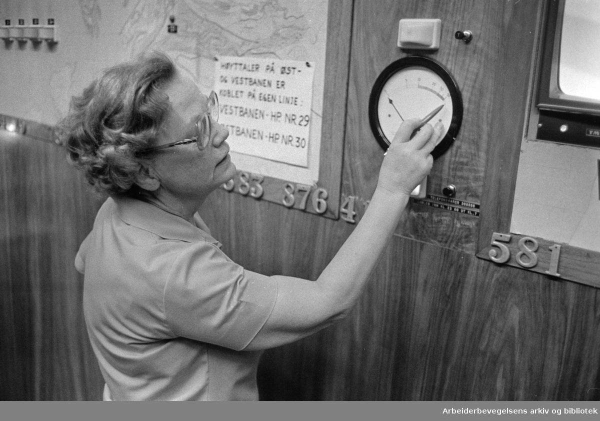 Drosjesentralen. Vaktsjef Ragnhild Bekkby på drosjesentralen viser fram meteren som viser pågangen av telefoner. Desember 1975.