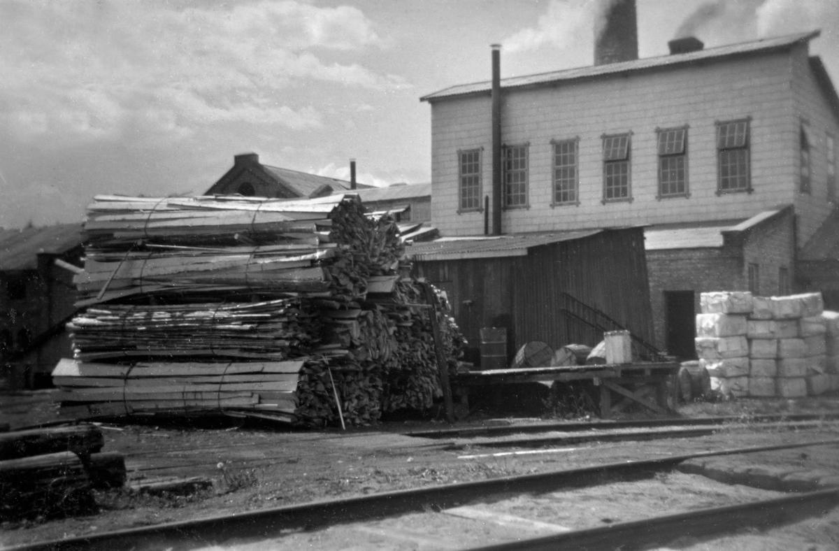 Bildet er tatt ute på fabrikktomta fra øst mot fabrikkbygningene på Klevfos Cellulose- & Papirfabrik.  En ser noen honbunter med langhon i forgrunnen. Fabrikken brukte cirka 5000 kubikkmeter bakhon tidlig i 1960-årene.  Dominerende i bildet er det karakteristiske overbygget, med seks vinduer på langveggen, over det nye lutinndampingsanlegget. Lutinndampingsanlegget ble innkjøpt brukt fra Torp Brug i 1955. I august 1956 kom prøvedriften av anlegget i gang. Bygget over anlegget som kom på plass i 1955/1956 hadde først bordkledning. Denne bordkledningn ble seinere påført vedlikholdsfire eternittplater. Da dette bildet ble tatt var veggene kledt med vedlikeholdsfrie eternittplater.   Bildet er udatert, men det grunn til å tro at det er tatt en gang i tidsrommet 1959-1963. Det er derfor grunn til å betrakte bildet som en illustrasjon på hvordan fabrikkanlegget så ut omkring 1960.  Løten. Ådalsbruk.