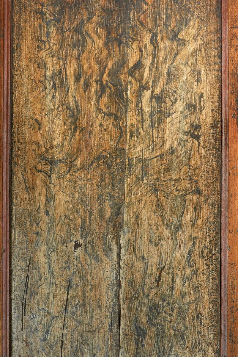 Bemalt trespeil i skapdør i «Austmostua» eller «Østmostua» på Glomdalsmuseet i Elverum.  Denne bygningen er egentlig fra Mogrenda på Vestsida i Hoff i Solør, men den ble demontert og gjenreist på museet i 1919. Det er noe uvisst om dette skapet fulgte med huset, eller om det kan være fra en annen eiendom i Solør.  På dette fotografiet (som er tatt på høykant) ser vi kantene av to av rammetrærne i dørkonstruksjonen, som begge møter det planhøvlete dørspeilet med en profilert kant.  Rammetrærne er malt i en rødbrun farge, men sjølve speilet har en gulaktig grunntone med en viss årringstruktur, som synes å være lasert med en gråere farge i et slags siksakmønster.    Austmobygningen (jfr. SJF-F. 006768) er en 10, 7 meter lang og 9 meter bred laftet svalgangsbygning med torvtekket saltak.  Første etasje har såkalt akershusisk grunnplan med inngang til et stuerom med dører videre til to mindre rom, et kjøkken og et kammers i den andre enden av bygningen. Annen etasje er delt i to rom, som har separate dører mot svalgangen.  Den bæres av dreide stolper.  Oppgangen til annen etasje skjer via ei trapp med repos i den ene enden av svalgangen.  Skapet med den fotograferte døra står i det rommet som er innredet som kjøkken, der det antas å ha fungert som matskap.  Håvard Skirbekk har i boka «Hus og tun» (1963) gjengitt et skiftedokument (side 298-299) som forteller hvordan huset var møblert i 1791.  Her nevnes et «Dørskab i Stuen», men om dette skapet er det samme som vi ser på fotografiet, vet vi ikke.  Nettopp dødsfall med påfølgende skifteoppgjør – som førte til at løseøre ble fordelt på ulike kreditorer og arvinger eller auksjonert bort og dermed konvertert i penger – førte jo til at møbler «vandret» fra gard til gard.   Fotografiet er tatt som illustrasjonsforslag til en artikkel som tar utgangspunkt i en dølgsmålsfødsel som skjedde på Veltstu Austmo, muligens i denne bygningen, i 1782.