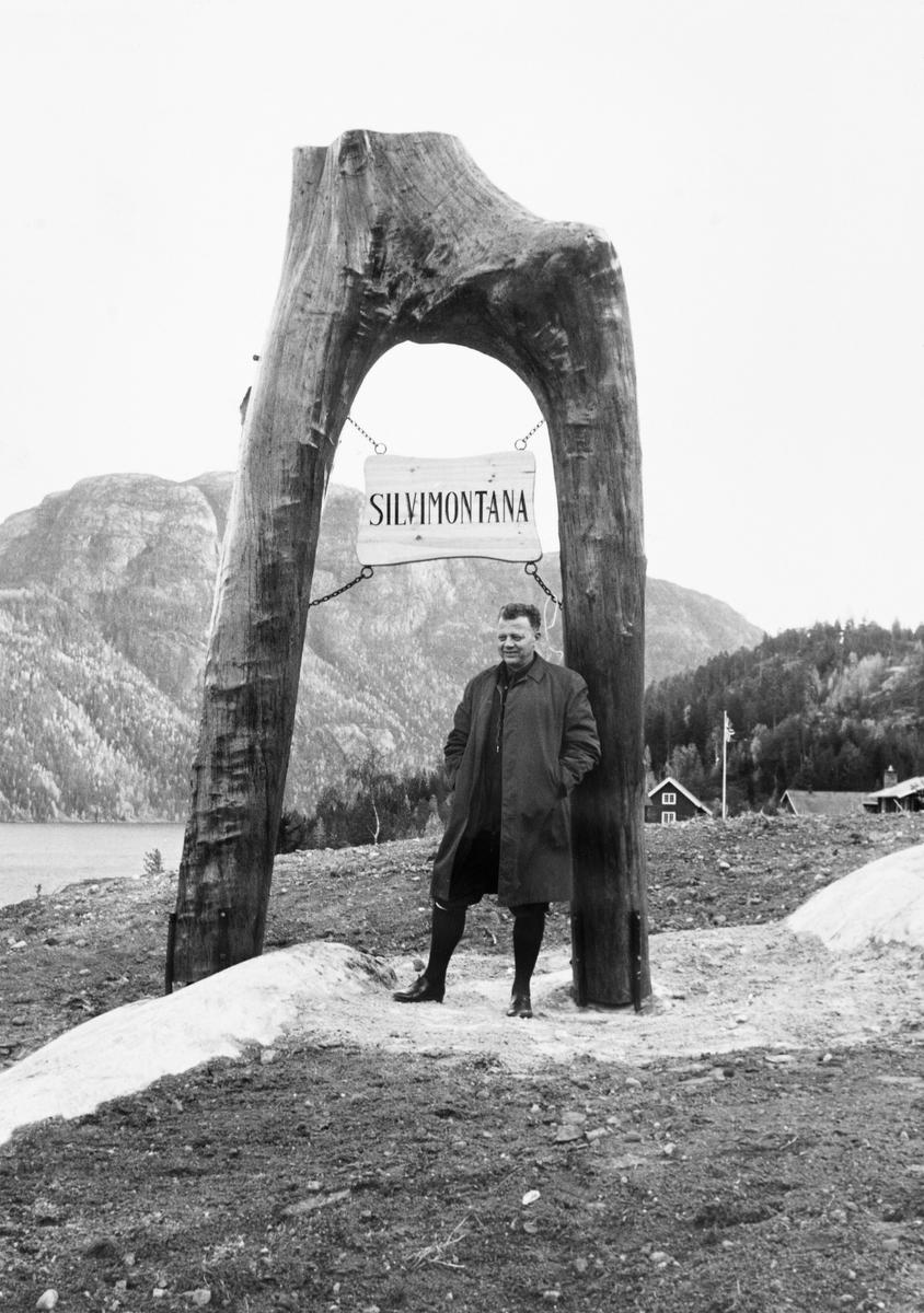 Venstrepolitikeren Hallvard Eika (1920-1989), fotografert ved portalen som markerte innkjørselen til forskningsstasjonen «Silvimontana» i Kvitesed i Telemark.  Fotografiet er tatt på innvielsesdagen, 20. oktober 1970.  På dette tidspunktet var Venstre-mannen Hallvard Eika landbruksminister i Per Bortens borgerlige samarbeidsregjering, og det var antakelig denne posisjonen kombinert med et str engasjement for hjemfylket Telemark som gjorde at Eika fikk oppgaven med å avduke navneskiltet.  Dette besto av ei rektangulær treplate hvor navnet var påført med svarte bokstaver.  Plata han i ei kraftig trekløft, som var barket, beiset og montert opp-ned, slik at det nevnte skiltet kunne henge i fire kjettingstubber oppunder den buen kløfta dannet.  Eika poserte under skiltet.  I bakgrunnen skimter vi gamle og nye hus på småbruket Lindestad, som i og med den seremonien Eika nettopp hadde bidratt til skiftet navn til «Silvimontana» og funksjon til å bli et senter for driftstekniske undersøkelser knyttet til skogbruk i bratt terreng.  Skogeiersamvirket hadde bistått den driftstekniske avdelingen i Norsk institutt for skogforskning med penger til et nytt hus som skulle romme verksteder og lokaler for forskning og formidling.  Så vel etablerte fagfolk som studenter som besøkte Silvimontana for å delta i undersøkelser eller kurs ble også innkvartert i det gamle våningshuset fra småbruksfasen på Lindestad.  Det var godseier Severin Diderik Cappelen (1892-1980) som stilte eiendommen til disposisjon professor Ivar Samset (1918-2015) og kollegene hans mot en meget rimelig leiesum.  De fleste undersøkelsene som ble gjort i Kviteseid dreide seg om taubanedrifter og annen tømmertransport i bratt terreng.  Mer informasjon om Silvimontana og de undersøkelsene som ble gjort der finnes under fanen «Opplysninger».