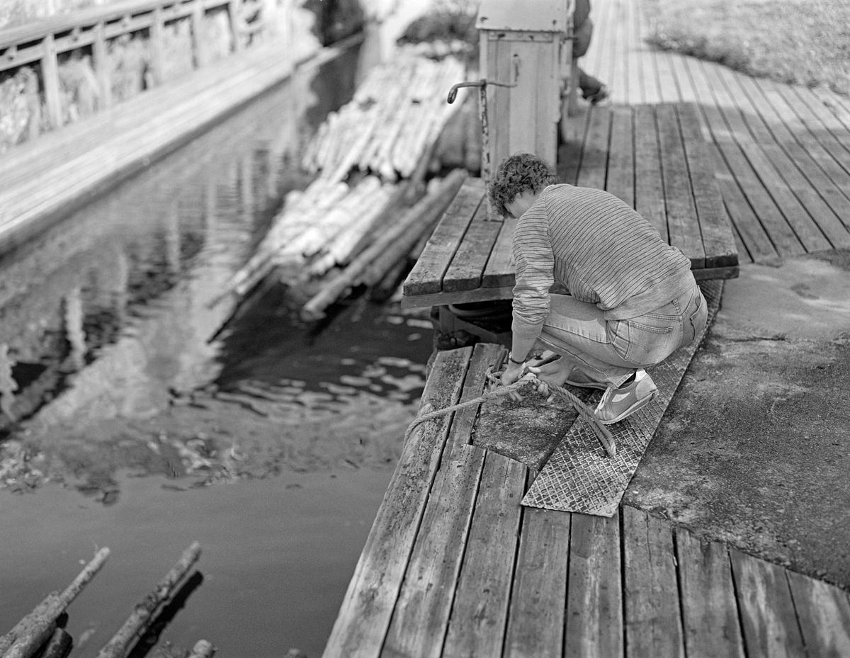 Fra Strømsfoss sluse i Aremark i Østfold.  Fotografiet er tatt høsten 1982, som var den siste sesongen det ble fløtet tømmer i Haldenvassdraget.  I forgrunnen sitter Anne Johansen på huk og binder et tau til en jernring i betongen like ved innhengslingsstedet for den østre halvdelen av øvre sluseport.  Tauet er sannsynligvis også knyttet til et av bindene på den bakerste tømmerbunten i ei slusevending som nettopp har fått flyte inn i slusekammeret.  Der var det viktig å forankre tømmeret, slik at det ikke drev for langt fram i slusekammeret, og dermed ble i veien når nedre sluseport skulle åpnes, for å slippe slusevendinga over i underkanalen.  Strømsfoss sluse hadde bare ett slusekammer.  Det utliknet en høydeforskjell på cirka to meter mellom kanalen fra den ovenforliggende Strømselva og kanalen mot Aremarksjøen på nedsida.  Strømsfoss sluse hadde mye trafikk, og derfor hadde Haldenvassdragets Kanalselskap mekanisert driften ved hjelp av hydrauliske systemer for åpning og lukking av porter og luker.  En liten historikk om tømmerfløting og kanaliseringsarbeid i Haldenvassdraget finnes under fanen «Opplysninger».