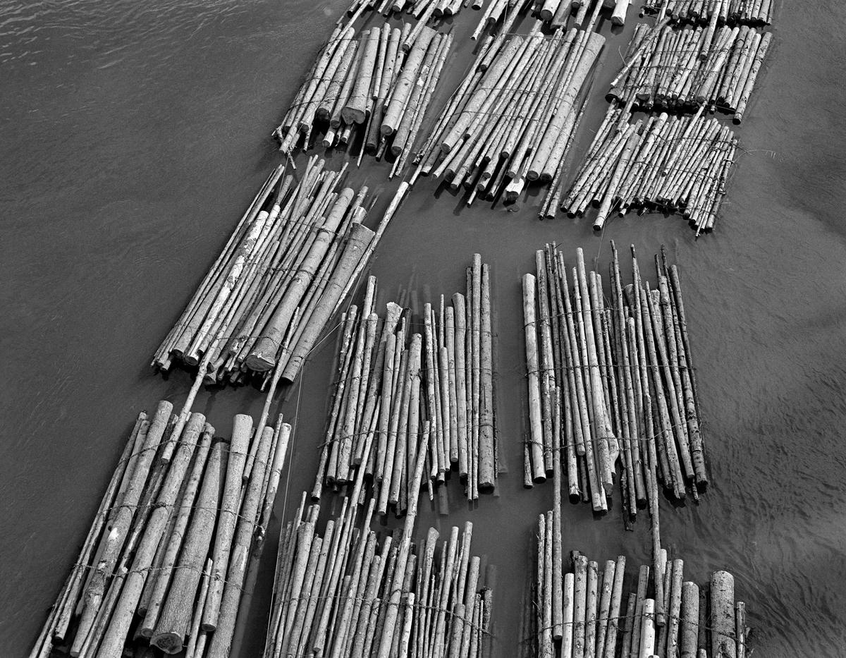 Detalj fra tømmerslep i Skotsbergelva i Aremark kommune i Østfold.  Fotografiet er tatt fra brua der riksveg 21 krysser vassdraget, noe som har muliggjort et fugleperspektiv på tømmeret nede på vannspeilet.  Her ble det fløtet buntet, ubarket massevirke av gran i tre meters lengder.  Buntene var egentlig lastebillass, som det ble slått tre, av og til fire, vaierbind rundt før de ble slått til vanns høyere oppe i vassdraget.  Over de store innsjøene ble tømmeret buksert i digre slep bak kraftige slepebåter.  Skotsbergelva er en cirka fire kilometer lang elvestrekning mellom Aremarksjøen (Ara) og Aspern.  Etter oppdemminga og kanaliseringa av vassdraget med dammer og sluseanlegg i Stenselva ved Krappeto og Brekke ligger de to nevnte sjøene om lag på samme høyde (105 meter over havet). Skotsbergelva er følgelig et forholdsvis stilleflytende elveløp hvor det var greit å slepe tømmer, sjøl om det var litt trangt i det partiet som kalles «Tordivelen».  Derfor måtte slepets bredde begrenses til tre parallelle tømmerlenker her.  Fotografiet ble tatt i 1982, som ble den siste fløtingssesongen i Haldenvassdraget.  En liten historikk om tømmerfløting og kanaliseringsarbeid i Haldenvassdraget finnes under fanen «Opplysninger».