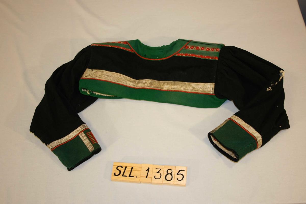 Langerma trøye av klede, med stutt rygg, broderi og glasknappar framme og på mansjettane. Sølvborder framme på ermane og nede på ryggen.