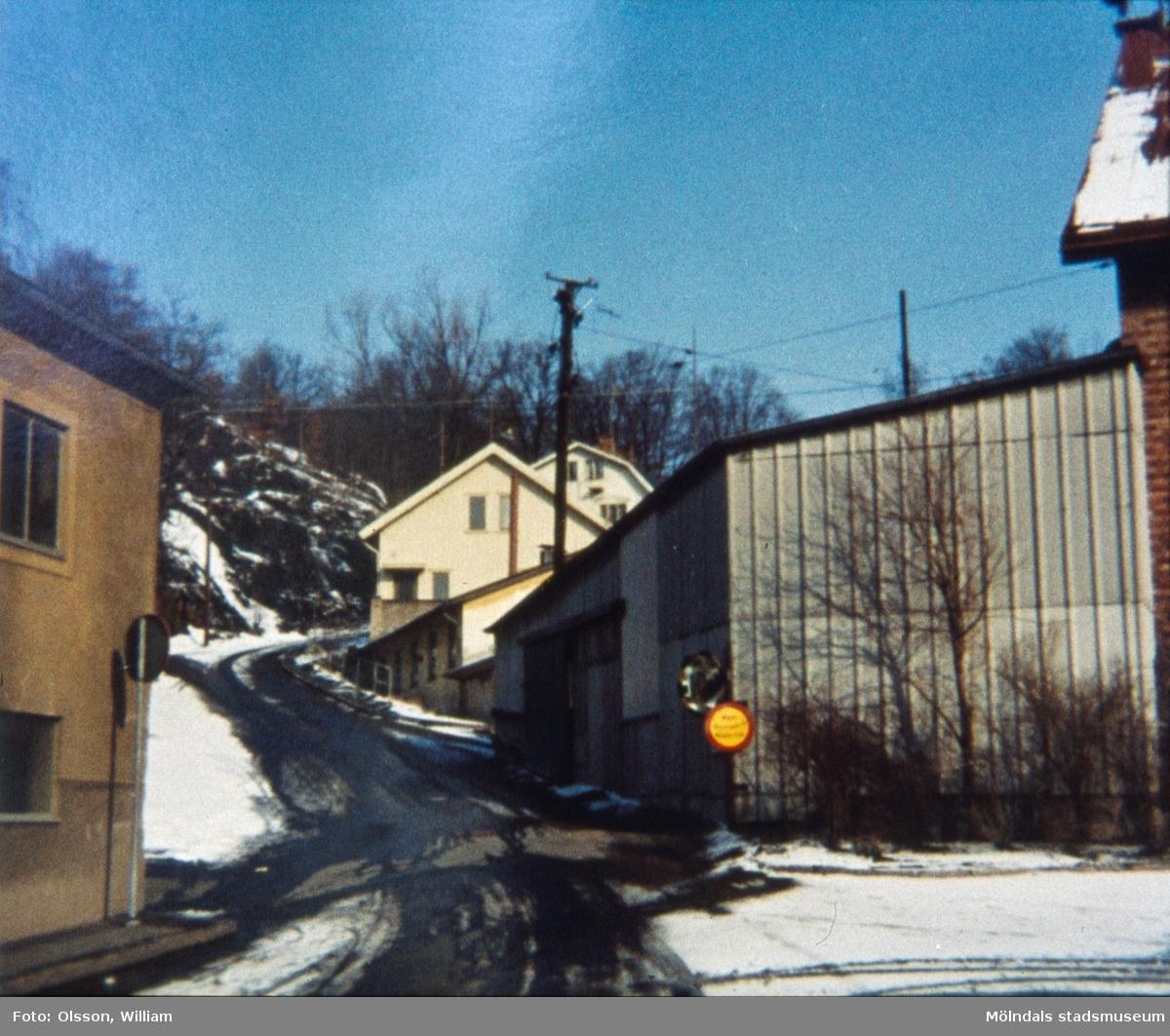 Samuel Norbergsgatan – Friareliden, okänt årtal. En backe svänger åt höger utefter Störtfjället. Fabriksbyggnad ses till vänster och garage samt villor till höger. Elledningar passerar över byggnaderna och det är snö och halka på marken.