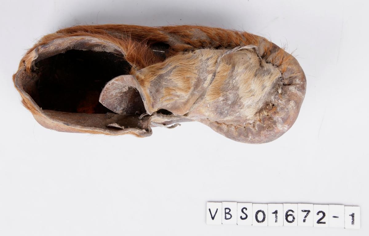 Venstre sko fra skopar. Hårsiden ut, med pels. Skoene består av fire deler, en såle, en del som dekker vrist og to deler med midtsøm vertikalt på hælen. Alle delene er sydd sammen med grov tråd. Snorer bindes over vristdelen, for å snøre skoen fast på foten.