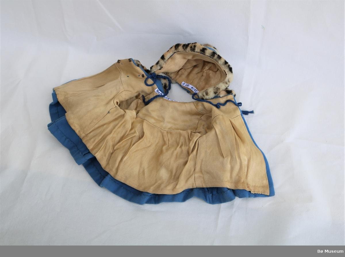 Dokke (a) i celluloid med kåpe, kyse og kjole. Dokka har støypt hår og auge som lukkar seg når det ligg flatt. Hår og ansikt er måla. Kåpa (c) og kysa (d) har pelskant med leopardlignande mønster. Kjolen (b) er pepitarutet, rekker til midt på låra, har krage, puffermer og snitt i livet. Løpegang med strikk i ermet. Kåpa er fora og har tre trykknappar. Foret heng laust i nedre kant.
